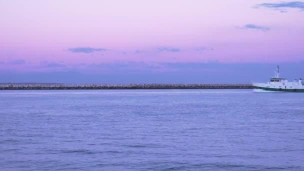 Rybářská loď přechází na řece při západu slunce