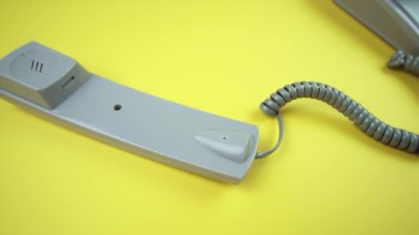 bezdrátový telefon s telefonem a šedým spirálovým drátem na žluté