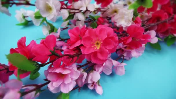 artificial sakura on branches on light blue background