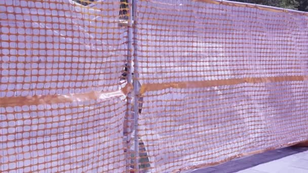 construction site fenced with orange grid and plastic sheets