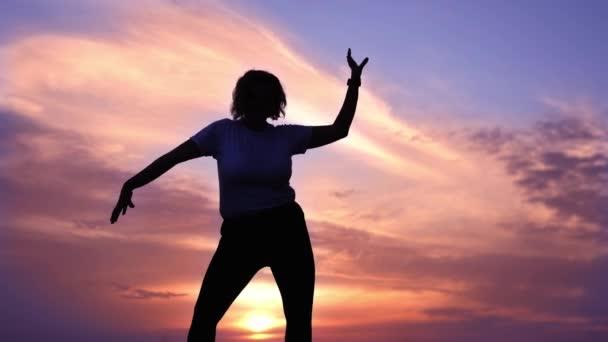 Dáma s krátkými vlasy tančí proti purpurové obloze při západu slunce