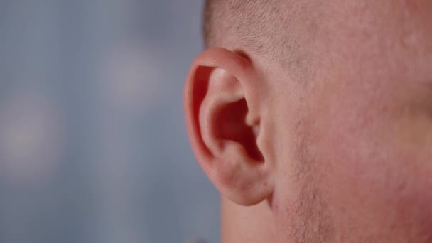 Kifejező kopasz ember azt mutatja, képes mozgatni a fülét a kék