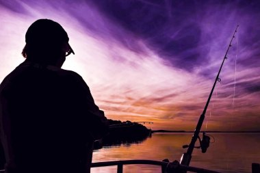 Fishing Lady Silhouette. Nephology image featuring colourful violet and orange sky cloud with sea water reflections from a mainly white tinted cirrus cloudy sky. Fame Cove, Port Stephens, Australia