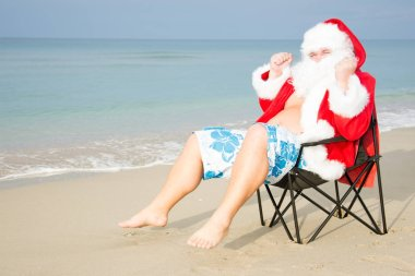 Funny Santa in shorts on the beach.