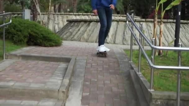 Mann beginnt mit einem Skateboard auf einem Stadthintergrund zu fahren