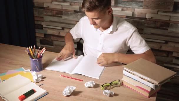 Student dělá úkoly. Hoch vypláče list papíru a hodí ho