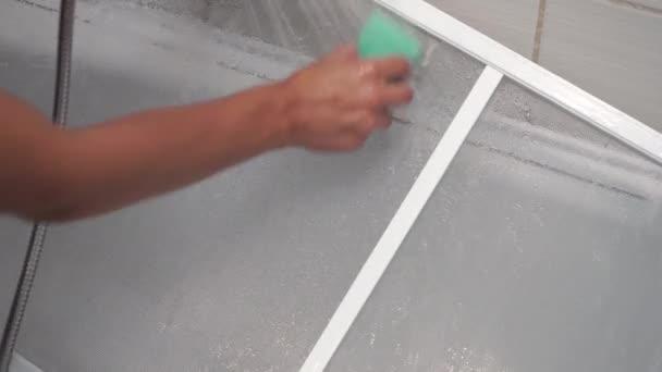 A szúnyogháló tisztítása a fürdőszobában vízzel és szivaccsal