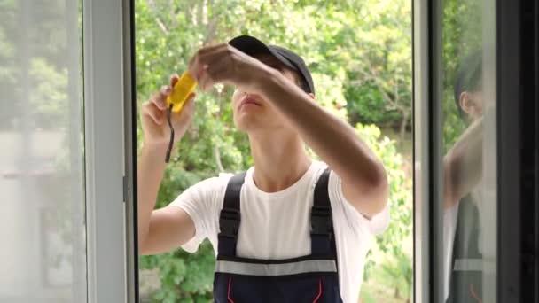 Mladý sklář měří okénko. Windows instalační pracovník, stavební pracovník sady kovových a plastových oken.