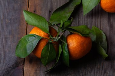 tangerines with leaves on pine boards