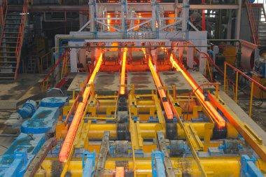Erimiş çeliğin dökülmesinden sonra, kırmızı çelik çubuklar. Devamlı döküm makinesi. Demirci ve metalurji endüstrisinin arka planı.