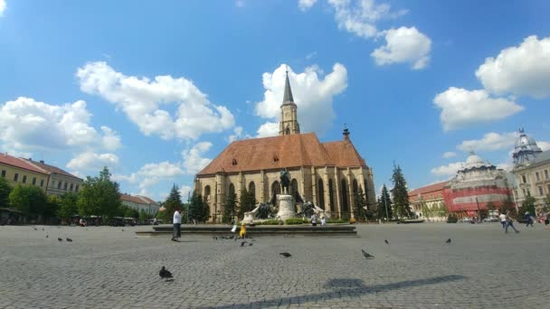 People walking on a beautiful sunny day on the pedestrian space next to the St Michael Catholic Gothic Church in Cluj-Napoca, Transylvania region of Romania with the Matei Corvin statue in the Unirii Square