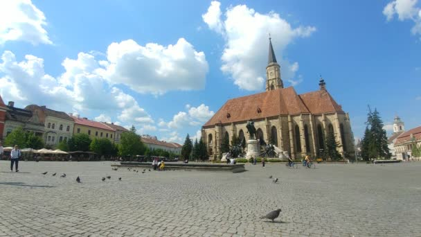 St Michael Catholic Gothic Church in Cluj-Napoca, Transylvania region of Romania with the Matei Corvin statue in the Unirii Square on a beautful sunny day with many people walking on this pedestrain space