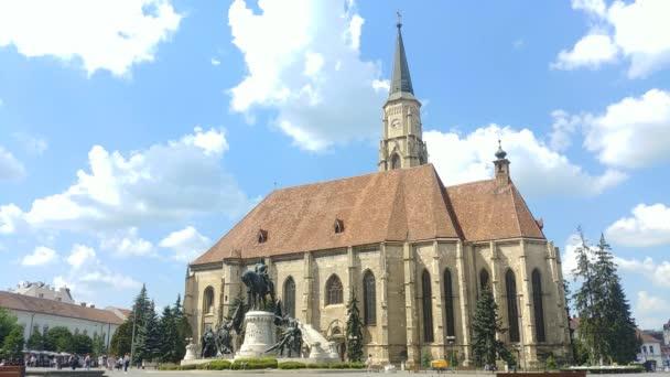St Michael Catholic Gothic Church in Cluj-Napoca, Transylvania region of Romania with the Matei Corvin statue in the Unirii Square