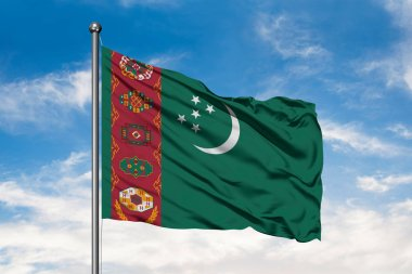 Flag of Turkmenistan waving in the wind against white cloudy blue sky. Turkmen flag.