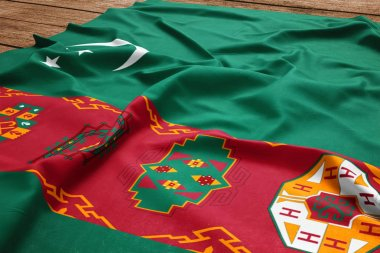 Flag of Turkmenistan on a wooden desk background. Silk Turkmen flag top view.
