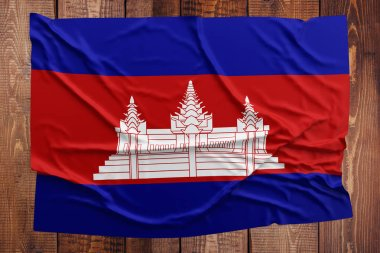 Flag of Cambodia on a wooden table background. Wrinkled Cambodian flag top view.