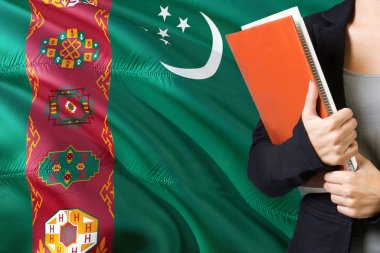 Learning Turkmen language concept. Young woman standing with the Turkmenistan flag in the background. Teacher holding books, orange blank book cover.