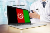 Afghanistan healthcare system in tech theme. Afghan flag on computer screen. Doctor standing with stethoscope in hospital. Cryptocurrency and Blockchain concept.