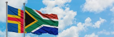Aland Islands and South Africa flag waving in the wind against white cloudy blue sky together. Diplomacy concept, international relations.