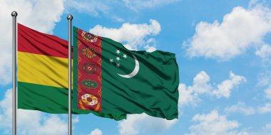 Bolivia and Turkmenistan flag waving in the wind against white cloudy blue sky together. Diplomacy concept, international relations.