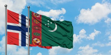 Bouvet Islands and Turkmenistan flag waving in the wind against white cloudy blue sky together. Diplomacy concept, international relations.