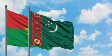 Burkina Faso and Turkmenistan flag waving in the wind against white cloudy blue sky together. Diplomacy concept, international relations.