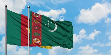 Cameroon and Turkmenistan flag waving in the wind against white cloudy blue sky together. Diplomacy concept, international relations.