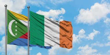 Comoros and Ireland flag waving in the wind against white cloudy blue sky together. Diplomacy concept, international relations.