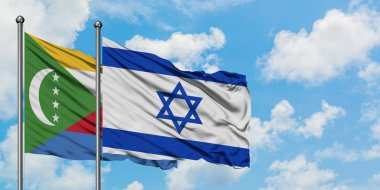 Comoros and Israel flag waving in the wind against white cloudy blue sky together. Diplomacy concept, international relations.