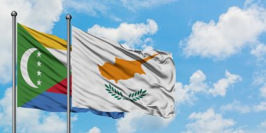 Comoros and Cyprus flag waving in the wind against white cloudy blue sky together. Diplomacy concept, international relations.