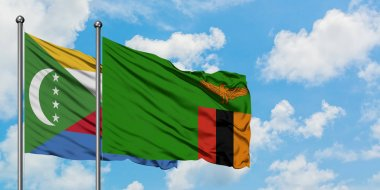 Comoros and Zambia flag waving in the wind against white cloudy blue sky together. Diplomacy concept, international relations.