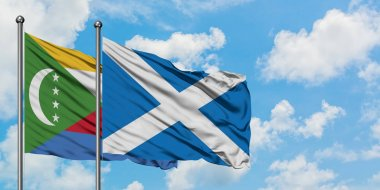 Comoros and Scotland flag waving in the wind against white cloudy blue sky together. Diplomacy concept, international relations.