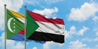 Comoros and Sudan flag waving in the wind against white cloudy blue sky together. Diplomacy concept, international relations.