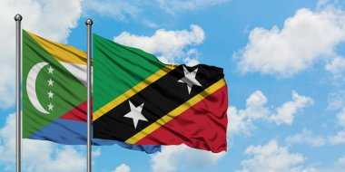 Comoros and Saint Kitts And Nevis flag waving in the wind against white cloudy blue sky together. Diplomacy concept, international relations.