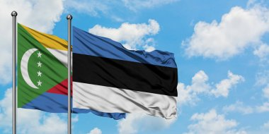 Comoros and Estonia flag waving in the wind against white cloudy blue sky together. Diplomacy concept, international relations.