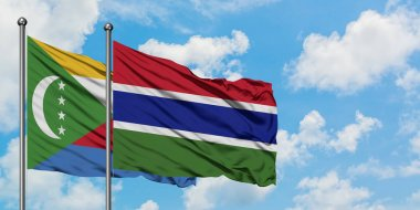 Comoros and Gambia flag waving in the wind against white cloudy blue sky together. Diplomacy concept, international relations.