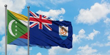 Comoros and Anguilla flag waving in the wind against white cloudy blue sky together. Diplomacy concept, international relations.