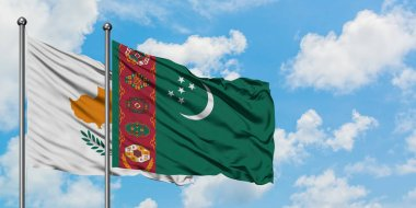 Cyprus and Turkmenistan flag waving in the wind against white cloudy blue sky together. Diplomacy concept, international relations.