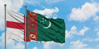 England and Turkmenistan flag waving in the wind against white cloudy blue sky together. Diplomacy concept, international relations.