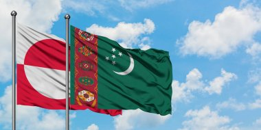 Greenland and Turkmenistan flag waving in the wind against white cloudy blue sky together. Diplomacy concept, international relations.