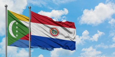 Comoros and Paraguay flag waving in the wind against white cloudy blue sky together. Diplomacy concept, international relations.