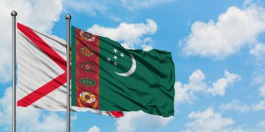 Jersey and Turkmenistan flag waving in the wind against white cloudy blue sky together. Diplomacy concept, international relations.