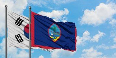 """Картина, постер, плакат, фотообои """"Флаг южной Кореи и Гуама развевается на ветру на фоне белого облачного голубого неба вместе. Концепция дипломатии, международные отношения."""", артикул 265614020"""