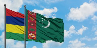 Mauritius and Turkmenistan flag waving in the wind against white cloudy blue sky together. Diplomacy concept, international relations.