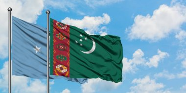 Micronesia and Turkmenistan flag waving in the wind against white cloudy blue sky together. Diplomacy concept, international relations.