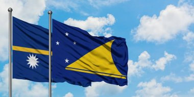 Nauru and Tokelau flag waving in the wind against white cloudy blue sky together. Diplomacy concept, international relations.