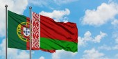 Fotografie Portugal and Belarus flag waving in the wind against white cloudy blue sky together. Diplomacy concept, international relations.