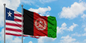 Fotografie Liberia and Afghanistan flag waving in the wind against white cloudy blue sky together. Diplomacy concept, international relations.