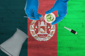 Fotografie Afghanistan flag on laboratory table. Medical healthcare technologist holding COVID-19 swab collection kit, wearing blue protective gloves, epidemic concept.