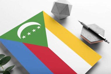 Comoros flag on minimalist paper background. National invitation letter with stylish pen on stone. Communication concept.